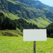 Blank signboard in a lush mountain valley — Stock Photo