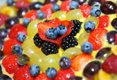 Colourful fresh fruit topping on a cake — Stock Photo