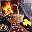 Autumn evening at fireside roasting chestnuts — Stock Photo #41295359