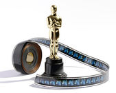 Replica Oscar statue with a roll of movie film — Foto Stock