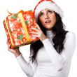 Beautiful girl in the hat of Santa Claus with a gift — Stock Photo #13256530
