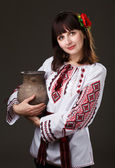 Beautiful woman in an embroidered shirt with a jug in his hands — Stock Photo