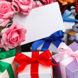 Greeting card with flowers and gifts — Stock Photo