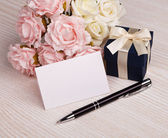 Greeting card with flowers and gift — Stock Photo