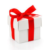 White gift box with red ribbon — Stock Photo