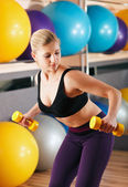 Beautiful blonde in sport gym with dumbbells — Stock Photo