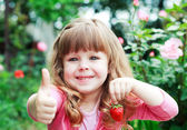 Little girl with strawberry, say OK — Photo