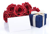 Greeting card with red flowers and gift box — Stock Photo