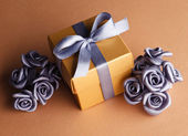 Artificial flowers and golden gift box — ストック写真