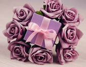 Violet flowers and gift box — Stock Photo