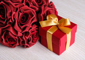 Red flowers and gift box with yellow ribbon — Stok fotoğraf