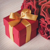 Red flowers and gift box — Stock Photo