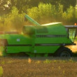 Stock Video: Combine harvester fill tractor trailer