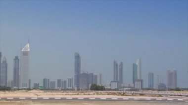 Small car cross Dubai skyline pan burj emirates 10299 — Stock Video