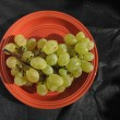 White grapes in a orange plate on black canvas background — Stockfoto