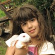 Portrait of happy little girl with adorable white rabbit — Stock Photo