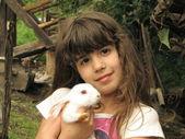 Porträtt av glad liten flicka med bedårande vit kanin — Stockfoto