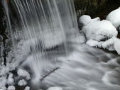 Waterfall, milky stream and ice — Stock Photo