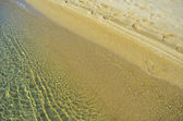 Golden sand and water — Stock Photo