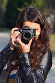 Young woman with DSLR camera — Stockfoto