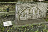 Fragment of tombstone with figures — Stock Photo