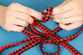 Handwork. weaving belt of satin ribbons — Stock Photo