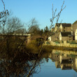 Houses reflection on Rivers edge - Stock Photo
