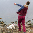Man throwing a stone into a Loch - Stock Photo