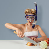 Young woman cutting onion in diving mask — Stok fotoğraf