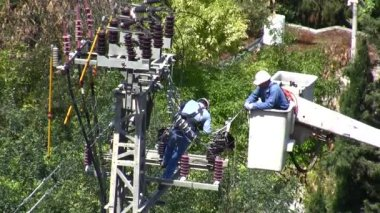 Two men, one of them in a bucket fixing electrical lines — Stock Video