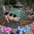 Stock Video: Chinese and world travelers enjoy hot springs below glacier for health