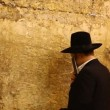 Orthodox Jewish Rabbi prays at the Western Wall in Jerusalem, Israel - Stock Photo