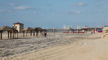 Couple walks across the sand of a Tel Aviv beach. — Vídeo de Stock