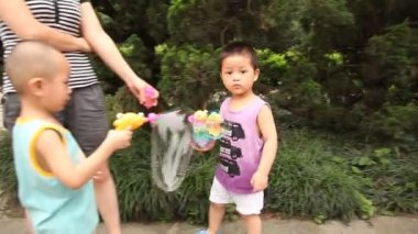 Chinese kids play with bubbles in the park — Stock Video