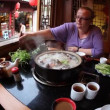 Tourist puts ingredients into steaming pot at a restaurant — Stock Video