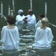 Stock Video: Baptism of pilgrims in JordRiver Holy Land Israel