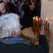 Stock Video: Pilgrims light candles baptismal site in JordRiver Holy Land Israel