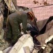 Stock Video: Female soldier searches for earthquake casualties digging through rubble