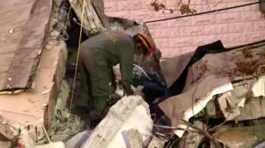 Female soldier searches for earthquake casualties digging through the rubble — Stock Video