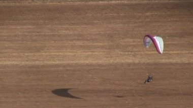 Motorized parachute lands on earth during competition of ultralight airplanes — Stock Video