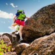 Woman climbs over a rock - Stock Photo