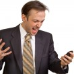 Angry businessman screams at phone — Stock Photo