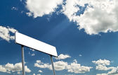 Sighpost with bright blue cloudy sky — Stock Photo