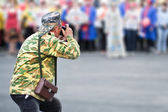 Photographer with old film camera takes reportage photo — Stock Photo