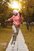Yound woman in red jacket jumps and have a fun — Zdjęcie stockowe