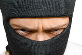 Close-up shot of angry man in black mask — Foto Stock