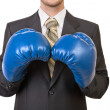 Businessman in black suit with boxing gloves — Stock Photo