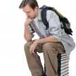 Male student with backpack sitting on the stack of books and thi — Stock Photo #45935557
