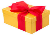 Single yellow gift box with red ribbon on white background — Stock Photo