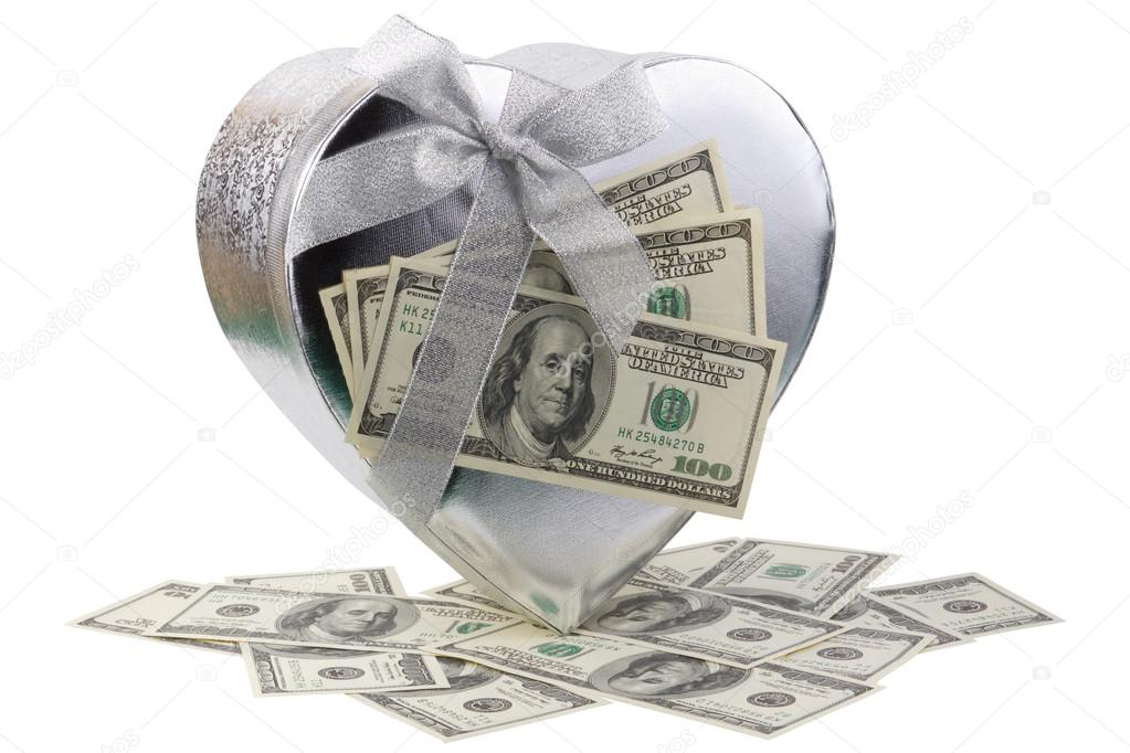 Best holiday bonus - single silver heart shape gift box and dollars on white background  Stock Photo #13402920